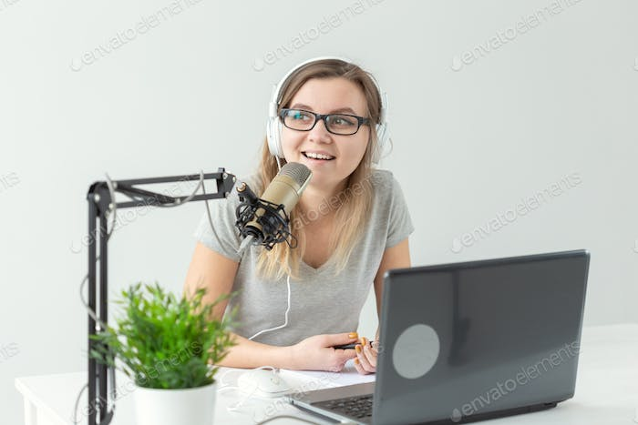 Female presenter working on the radio studio and talking on microphone