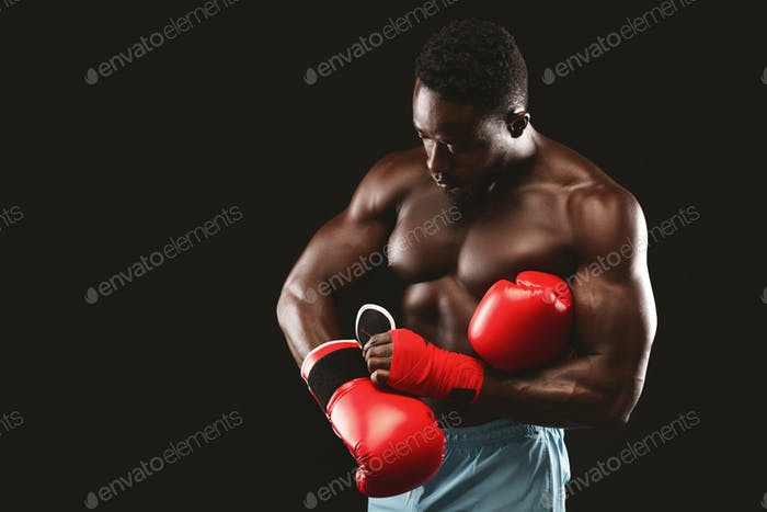 African muscular boxer wearing red gloves before fight