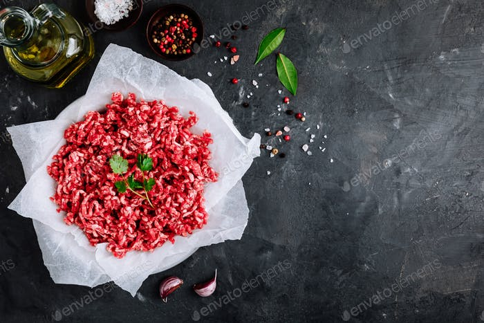 Raw ground minced meat and seasonings on dark background