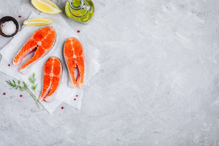 Fresh raw salmon steaks with lemon and dill for cooking on gray background.