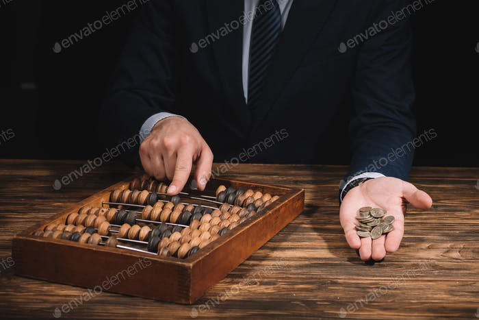 cropped shot of businessman holding coins and using abacus at wooden table