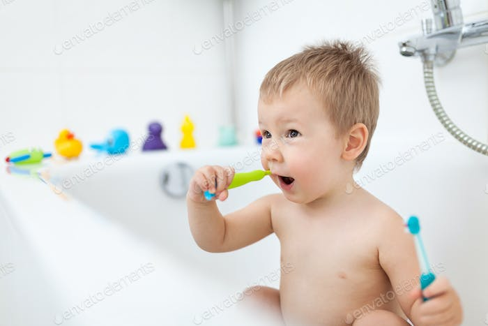 Adorable child learing how to brush his teeth