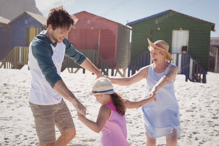 Happy multi-generation family holding hands at beach