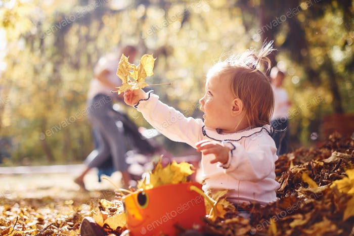 Cute little girl playing in the leaves at autumn park with her parents
