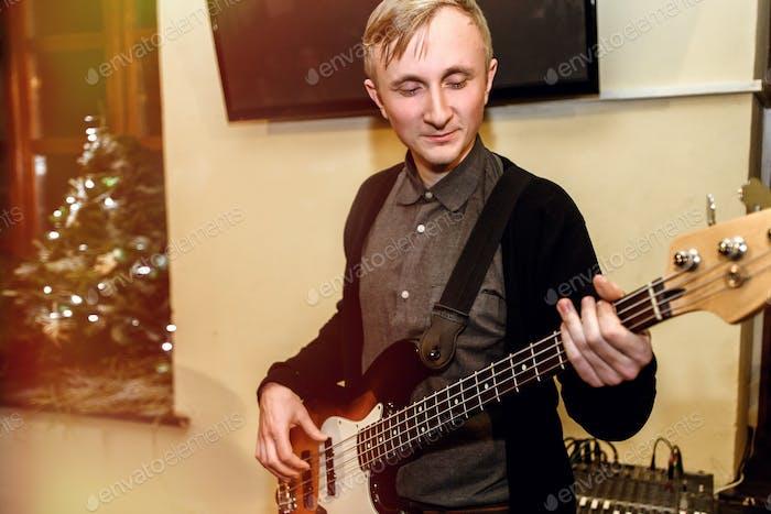 stilvoller Bassgitarrist spielt auf einem Konzert auf dem Hintergrund seiner Band