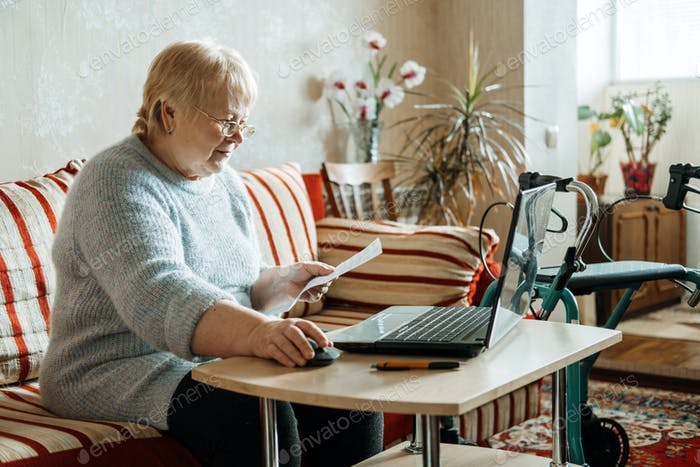 Life Insurance, Disability medical insurance policy for Seniors. Mature woman in glasses with Laptop