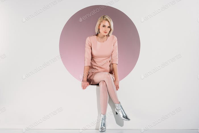 beautiful stylish blonde woman in dress and shiny shoes sitting in hole and looking at camera on