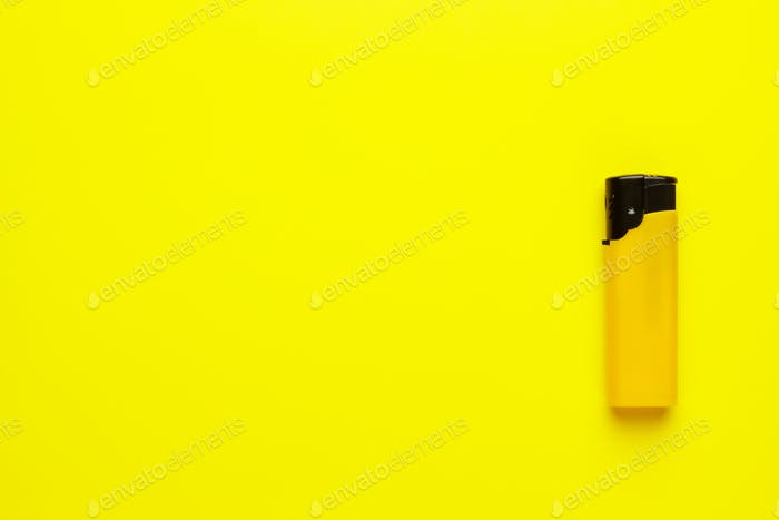 plastic lighter on yellow background