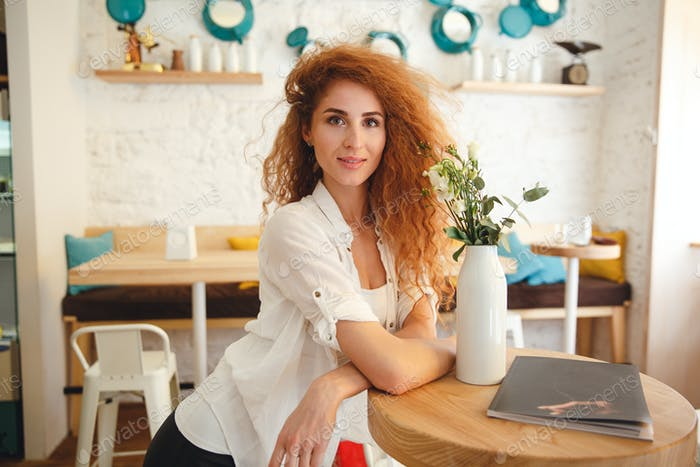 Gorgeous beautiful redhead young lady posing in cafe