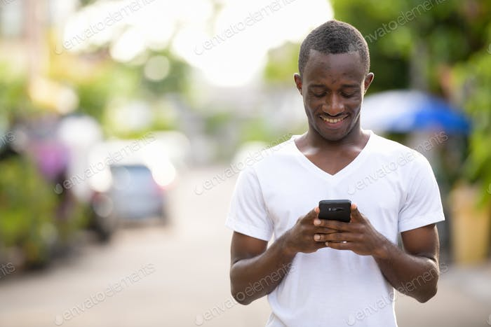 Young happy African man smiling while using phone in the streets outdoors