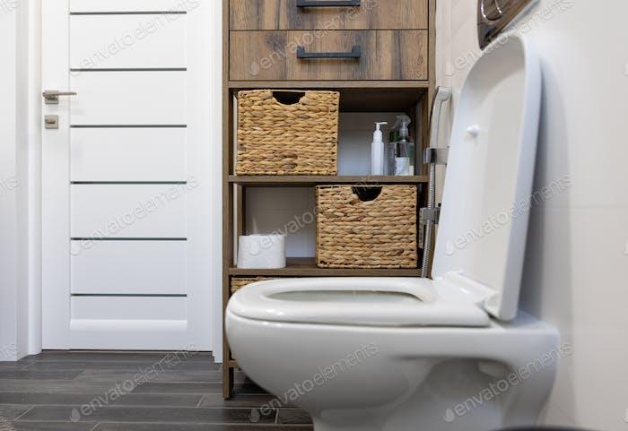 Toilet in the interior of a minimalistic bathroom.