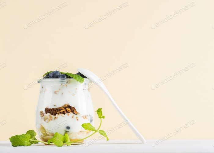 Yogurt oat granola with jam, blueberries and green leaves in glass jar on pastel yellow backdrop