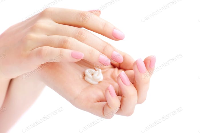 Young woman with pink manicure applies cream on her hands
