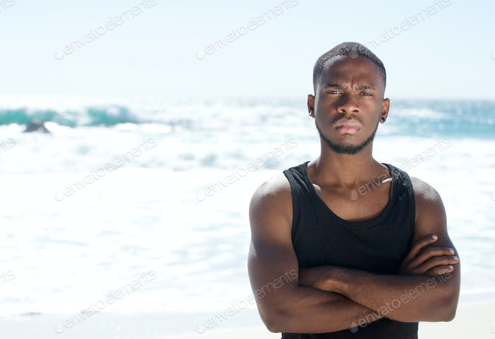 Attractive young man standing at the beach