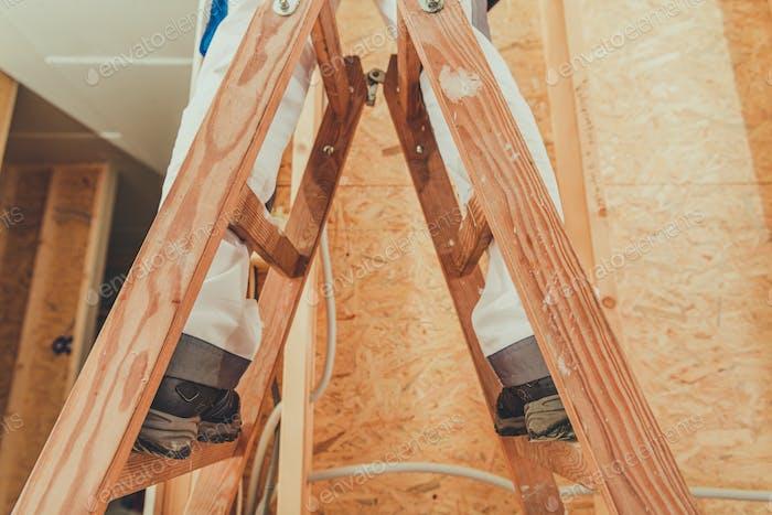 Trabajador de la construcción que se queda en escalera de madera