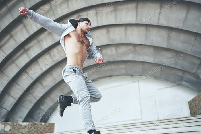 Ein junger Mann springt. Parkour im urbanen Raum, sportliche Aktivität
