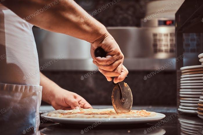 Chefkoch schneidet frisch zubereitete Pizza