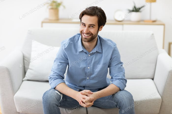 Guy Sitting On Sofa Smiling To Camera Posing At Home
