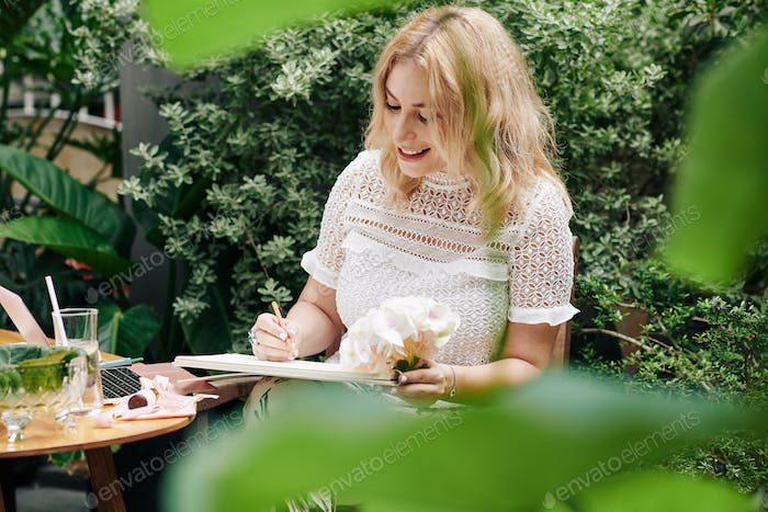 Smiling woman drawing flowers