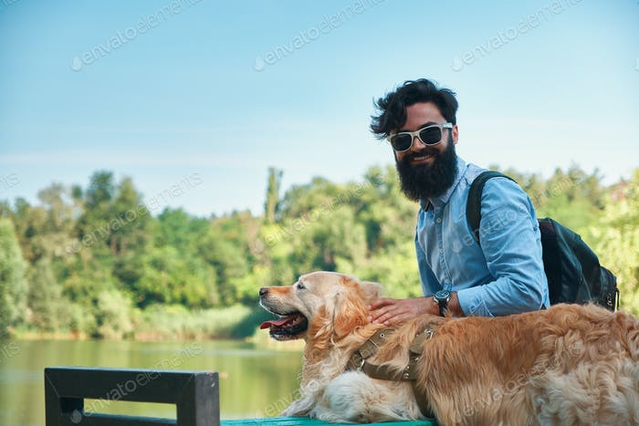 Young man sitting with his dog on the chair in the park hugging