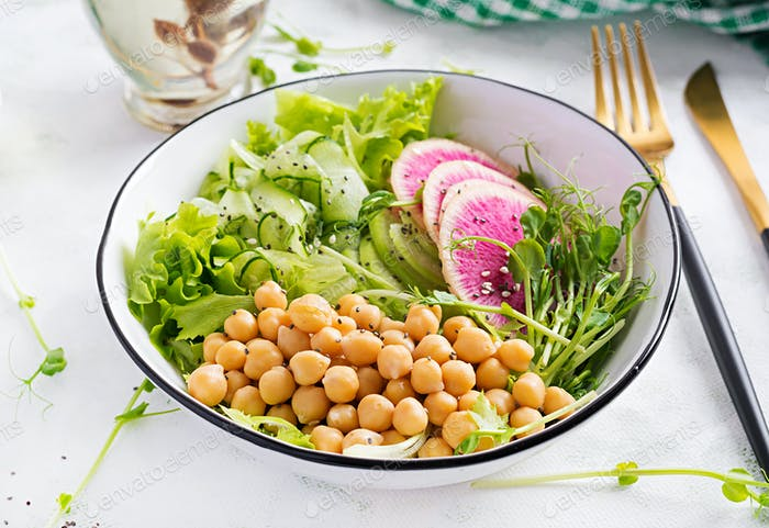 Vegan Buddha bowl with chickpeas, watermelon radish, cucumber and peas sprouts.