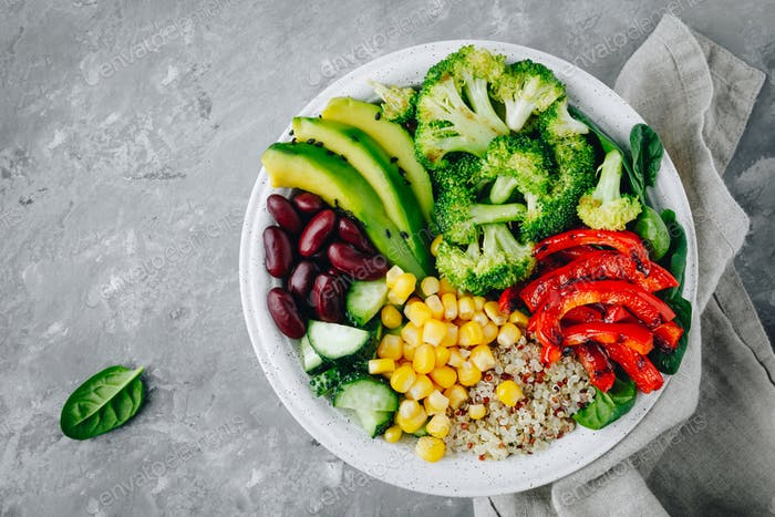 Healthy bowl salad with quinoa, spinach, avocado, beans, sweet corn, broccoli, cucumbers and paprika