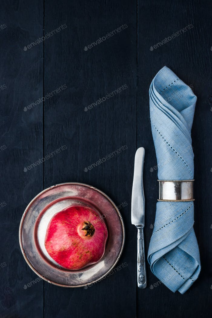 Pomegranate  on the vintage metal plate with knife and napkin vertical