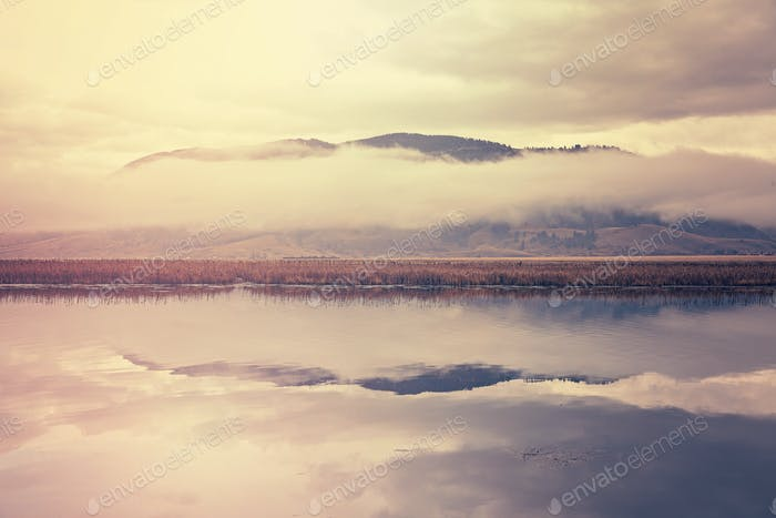 Retro toned foggy morning over lake in Grand Teton National Park