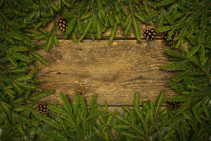 Christmas tree branches with cones on wooden texture ready for y