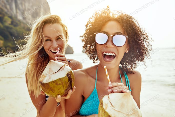 Two laughing friends drinking from coconuts on a sandy beach