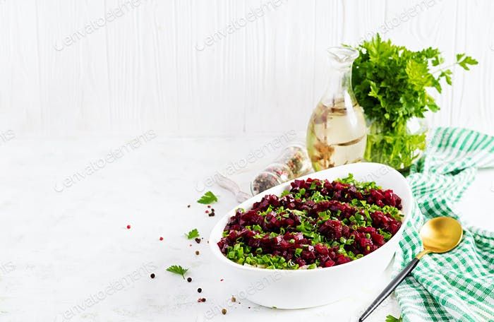 Kosher food, jewish salad. Herring,  pickled cucumber, beet, potato and apples salad on white  bowl.