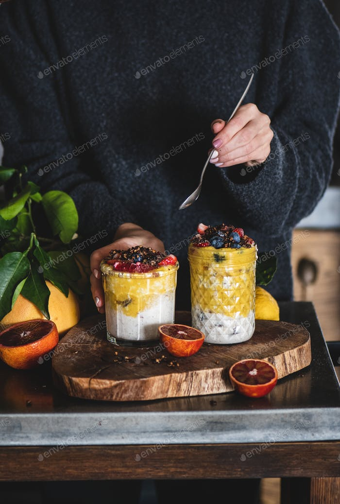 Woman eating healthy muesli with mango smoothie and granola