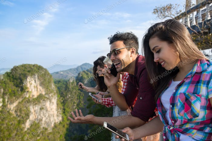 Young People Group In Mountain Using Cell Smart Phone Chatting Online Friends Asian Holiday Summer