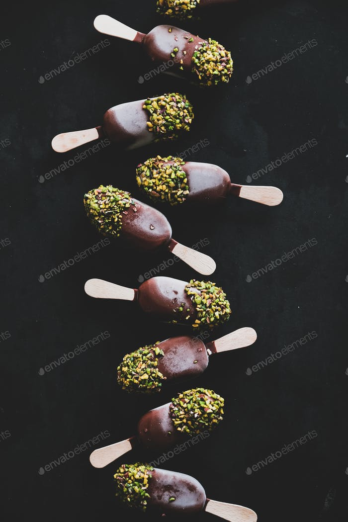 Chocolate glazed ice cream pops over black background