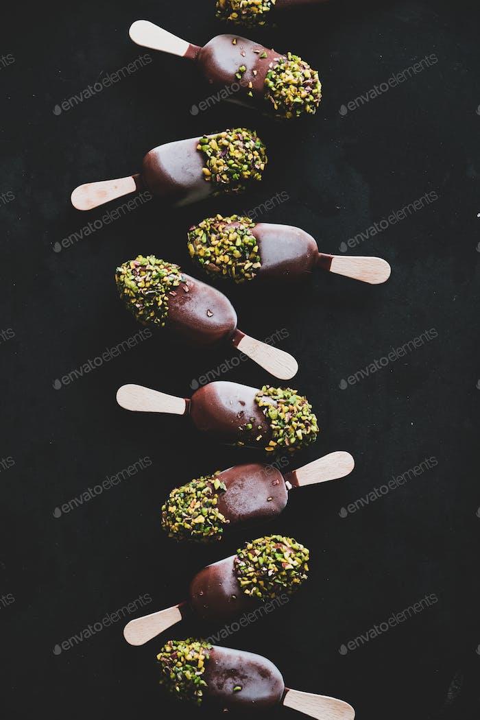 Schokoladenglasiertes Eis knallt über schwarzem Hintergrund