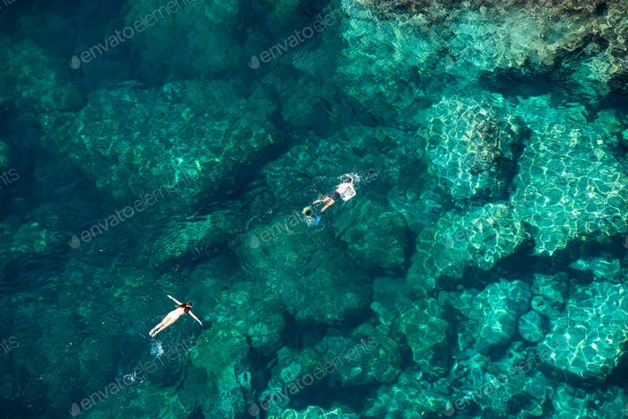Above view of a couple snorkeling in crystal clear sea water