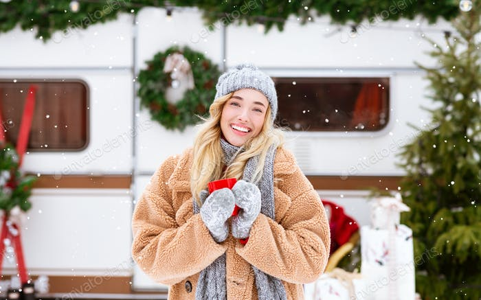 Winter Fairy Tale. Smiling Woman Drinking Tea Outdoors And Looking At Snowfall