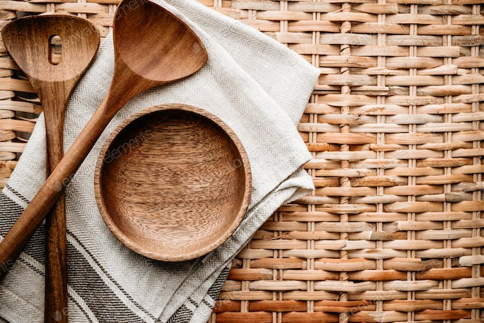 Cooking eco style background. Wooden kitchen tools and bowl on a rattan.