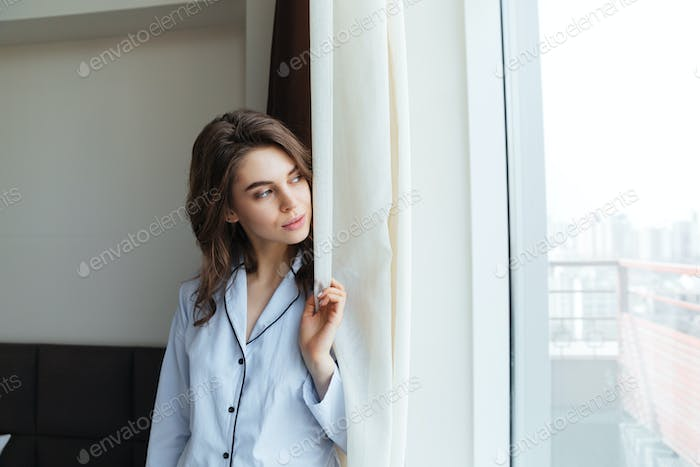 Young woman in pajamas facing the sunrise in the morning