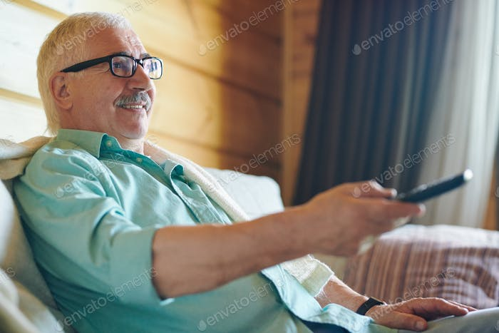 Cheerful senior grey-haired man in eyeglasses and shirt