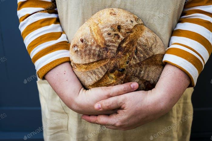 Nahaufnahme der Person, die einen frisch gebackenen runden Laib Brot hält.
