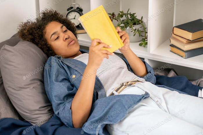 Pretty female student reading book while relaxing in bed