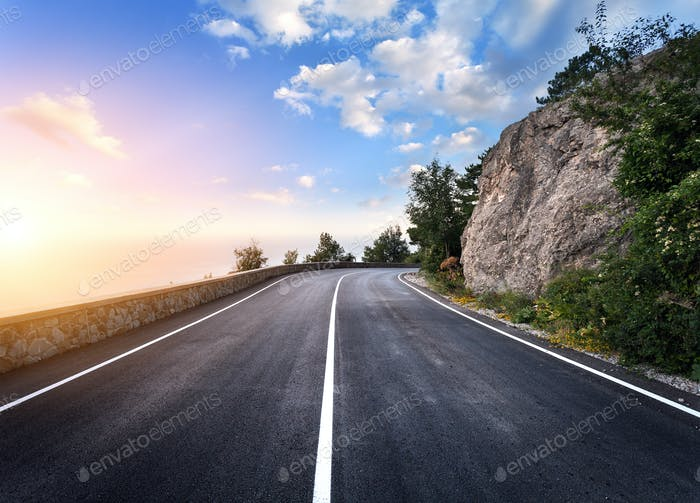 Beautiful mountain asphalt road with rocks, blue sky at sunset