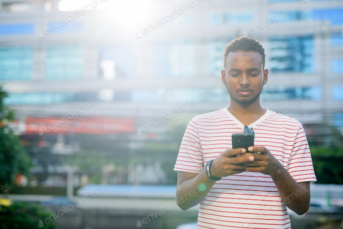Young handsome African bearded man using phone in the city