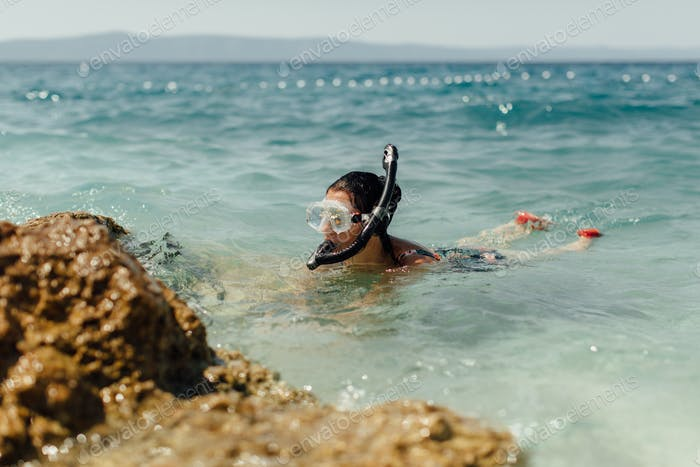 Female diver learning to dive at seashore.