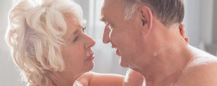 Elderly naked man looking at wife