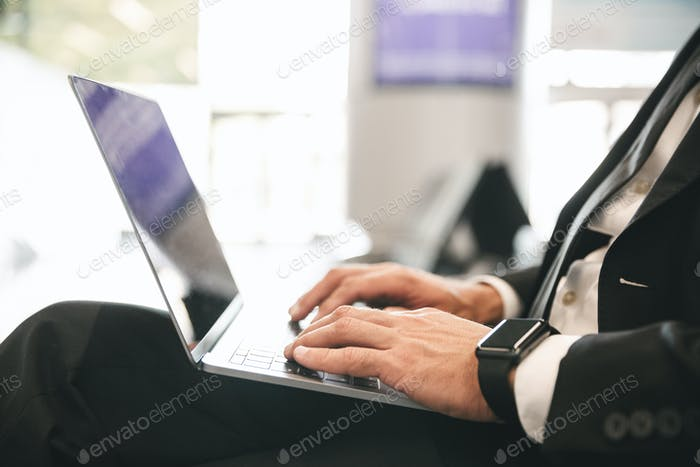 Close up of businessman dressed in suit typing