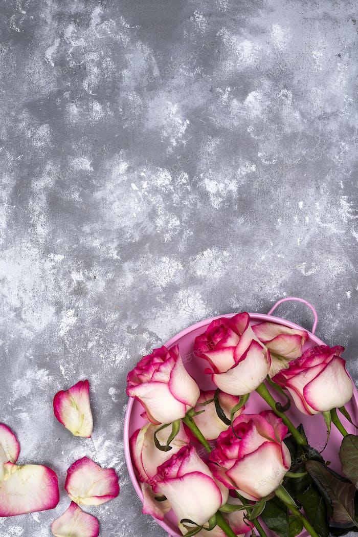 Красная белая роза букет с розовой подарочной коробкой на каменном столе.