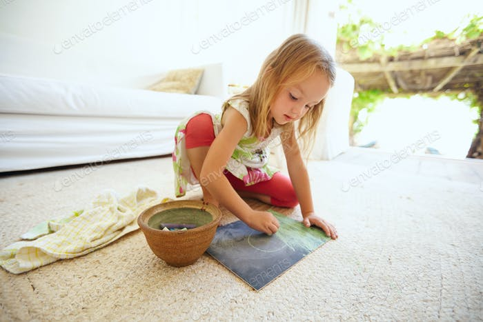Cute little caucasian girl drawing at home