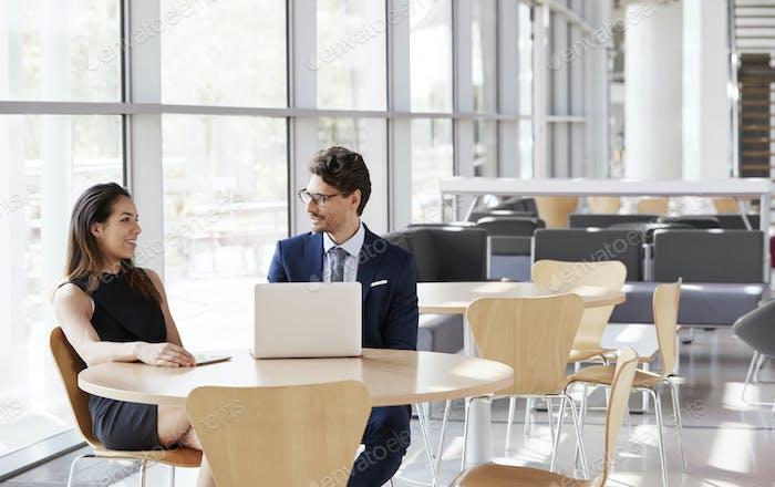 Geschäftsfrau und Geschäftsmann im Gespräch, Laptop auf dem Tisch